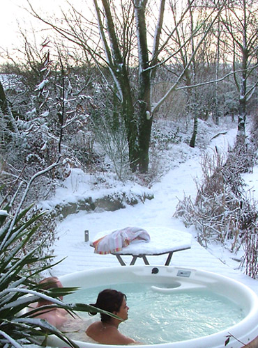 A couple sit in the hot tub in winter surrounded by snowy landscape.